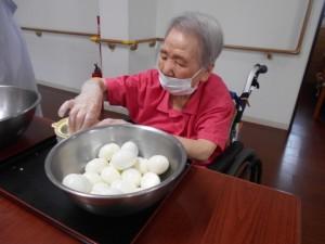 ゆで卵を専用の道具ですりつぶす作業